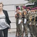 Беременная женщина проходит мимо солдат