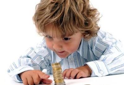 Мальчик строит башенку из монет (к статье о получении пособий непрописанному ребенку)