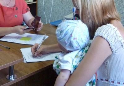 Молодая мама подписывает документы на пособие (к статье о получении пособий непрописанному ребенку)