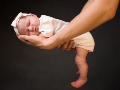 Родитель держит своего спящего ребенка на руках (к статье о получении пособий непрописанному ребенку)