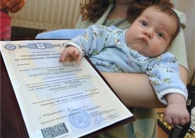 Сертификт на материнский капитал в руках у молодой мамы