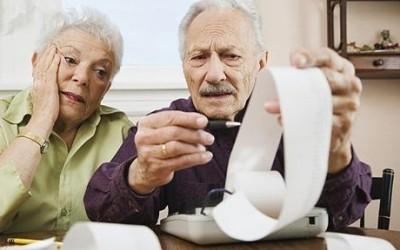 Бабушка с дедушкой рассматривают счета - к статье о льготах по налогам для пенсионеров