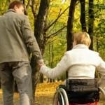 Женщина в инвалидной коляске с мужчиной на прогулке - к статье о трудовой пенсии по инвалидности